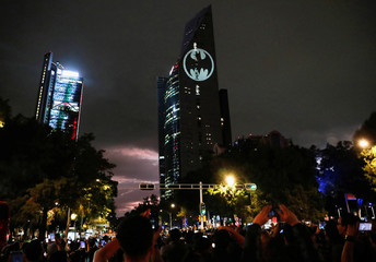 People take pictures of a Bat-Signal projected onto a building at night as Batman fans celebrate the 80th anniversary of the first appearance of the DC Comics superhero, in Mexico City