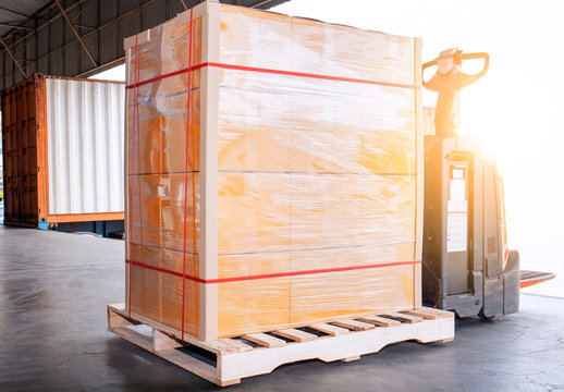 electric forklift pallet jack with goods pallet shipment, truck docking load cargo at warehouse, freight industry delivery, logistics and transportation.
