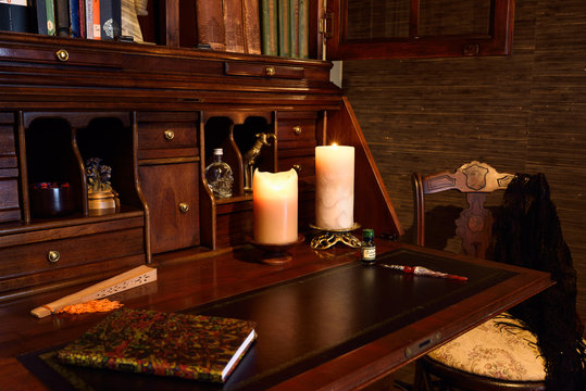 Antique secretary writing desk in dark room with candles