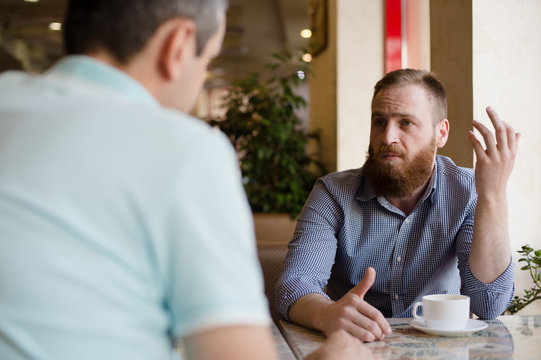 two men discussing difficult issues with emotions during coffee break in cafe talking about problems of business negotiation