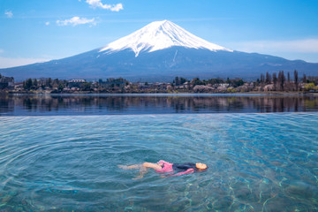 Wall Mural - Japanese girl swimming in hotel swimming pool with Fuji mountain background