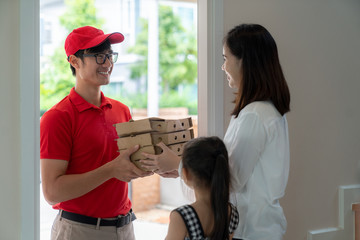 Asian woman recieve pizza box from pizza boy at the home