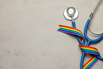 Stethoscope and LGBT rainbow ribbon pride tape symbol. Medical support after sex reassignment surgery. Grey background. Copy space for text.