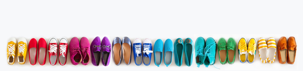 A lot of colored youth women's shoes without heels. Sneakers, slippers, ballet shoes. White background.