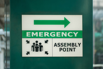 Emergency assembly point sign on the column of the building.