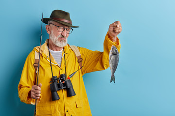 Picture of unhappy handsome old fisherman with blue eyes and beard holding fish, looking grumpy and dissatisfied, unhappy with poor catch. Hobby, leisure and occupation concept