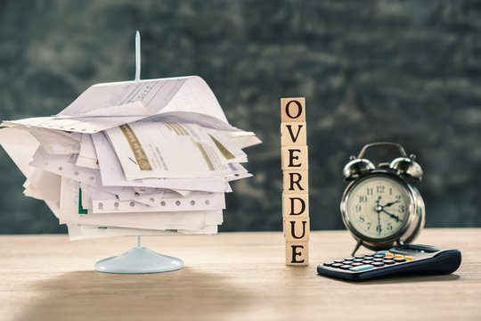 overdue concept with stack of unpaid bills ,calculator and clock on table