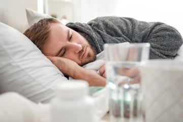 Obraz Man ill with flu lying in bed - fototapety do salonu