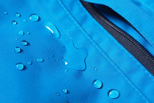 Closeup of water drops on bright blue fabric and black zipper with waterproof design to protect fabric of the cloth from humidity and to offer easy cleaning to users Fabric texture with design concept