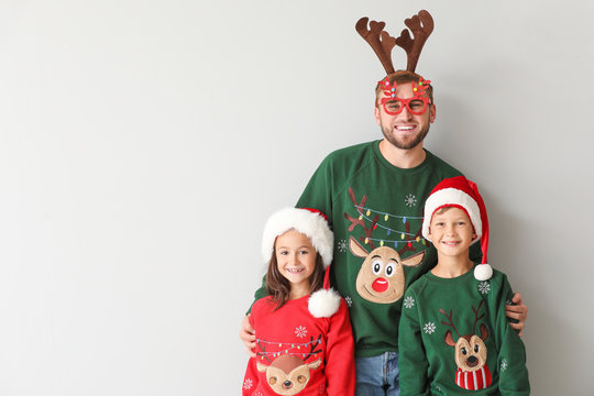 Funny man and his children in Christmas sweaters on light background