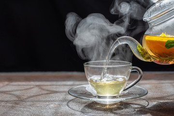 Foto op Plexiglas Thee Process brewing tea,dark mood.The steam from hot tea is poured from the kettle into a kettle with tea leaves redcurrant mandarin orange lemon,rosemary, mint.,hot food and healthy meal concept