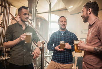 Three men tasting fresh beer in a brewery
