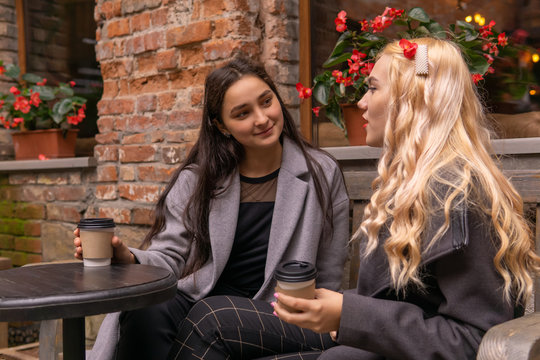 girl listens carefully to her friend on a bench with coffee outdoors