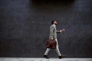 Full length of stylish caucasian designer in gray sweater holding leather bag while passing by gray...