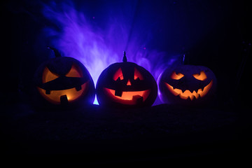 Group of Halloween Jack o Lanterns at night with a rustic dark foggy toned background