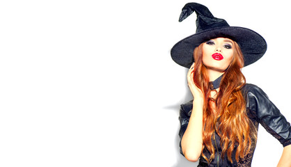 Halloween Sexy Girl wearing witch costume with a hat. Party, Celebrating. Beauty Woman with long red hair and holiday bright make-up isolated on white background. Leather dress Fototapete