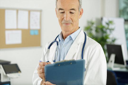 senior man doctor in white uniform holding clipboard