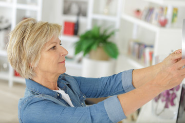 senior woman hanging a picture on the wall