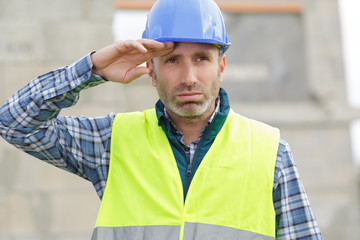 builder man with tired face wipes forehead