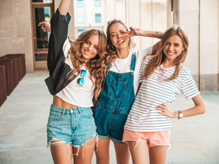 Portrait of three young beautiful smiling hipster girls in trendy summer clothes. Sexy carefree women posing on the street background.Positive models having fun.They raise hands Wall mural