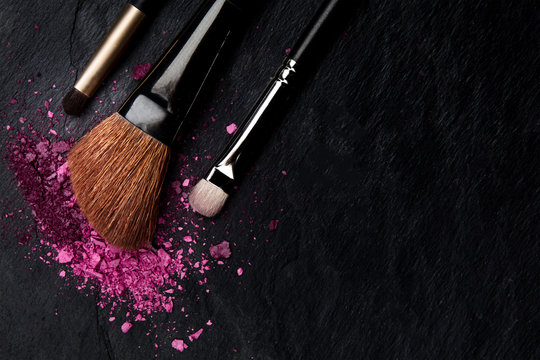 Make-up brushes with crushed cosmetics, shot from above on a black background with copyspace, a beauty design template for a makeup banner