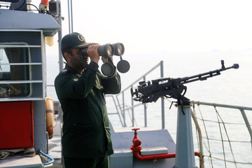 An IRGC officer looks through binoculars on a boat in coastal water during the annual military parade in Bandar Abbas