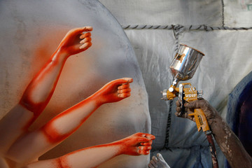 The hand of an artist is pictured as he sprays colour on an idol of Goddess Durga before selling it to a customer ahead of Dashain, a religious festival for Hindus in Lalitpur