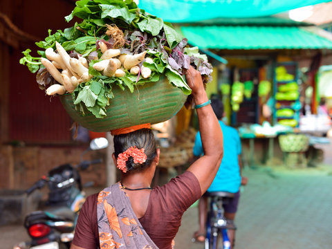 The women is carrying vegetables in the basket on the head Gokarna, the Karnataka.