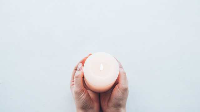 Peace and harmony. Top view of candle in lady tender hands over white background. Copy space.