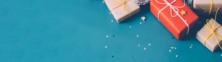 Winter holidays. Cropped flat lay of beige and red gift boxes, star and round shape glitter on teal blue background. Copy space.