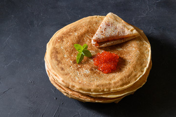 Stack of pancakes with red caviar on dark rustic background, top view