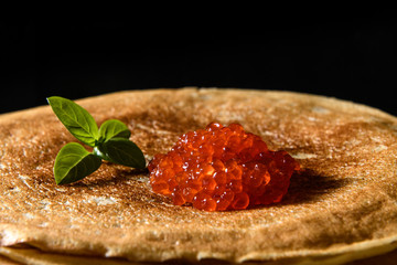 Stack of pancakes with red caviar on black background, close up