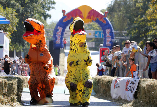 People wearing dinosaur costumes perform during the Red Bull Soapbox Race in Almaty
