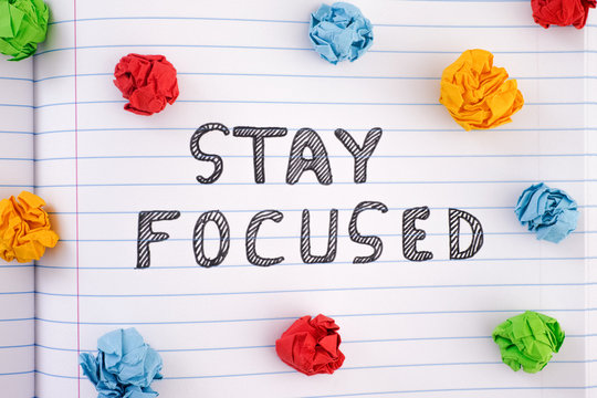 Phrase Stay Focused on notebook sheet with some colorful crumpled paper balls around it