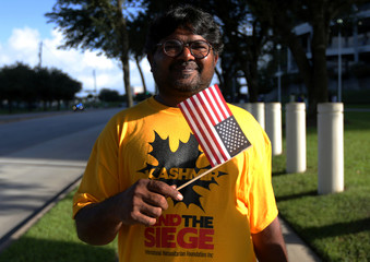 """A counter-demonstrator, who did not give a name, poses for a photograph during a """"Howdy, Modi"""" rally celebrating India's Prime Minister Narendra Modi at NRG Stadium in Houston"""