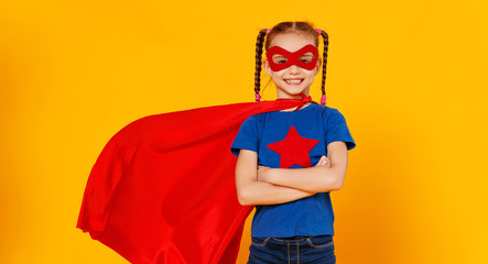 concept of child superhero costume on yellow background.