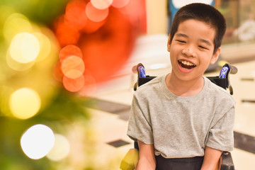 Asian special child on wheelchair smiling as happily with blurred lighting, Christmas Festival background, Life in the education age of disabled children, Happy disabled kid concept.