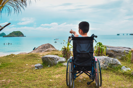 Asian special child on wheelchair is smile happily on the beach, Seaside nature background, blue sky and sand with day light,Life in the education age of disabled children, Happy disabled kid concept.