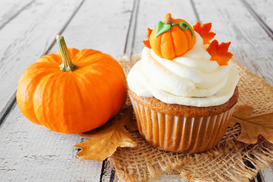 Fall pumpkin spice cupcake with creamy frosting and autumn toppings close up on a rustic white wood background