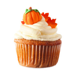 Fall pumpkin spice cupcake with creamy frosting and leaf and pumpkin toppings isolated on a white background