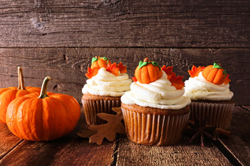 Fall pumpkin spice cupcakes with creamy frosting and autumn toppings. Scene against a rustic wood background.