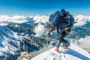Extreme alpinist in high altitude on Aiguille de Bionnassay mountain summit, Mont Blanc massif, Chamonix, Alps, France, Europe