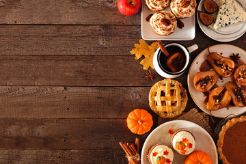 Autumn food side border. Table scene with a selection of pies, appetizers and desserts. Top view over a rustic wood background. Copy space.