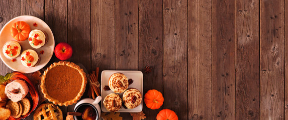 Aluminium Prints Autumn Autumn food corner border banner. Table scene with a selection of pies, appetizers and desserts. Top view over a rustic wood background. Copy space.