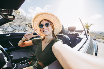 Happy young woman takes a selfie on a convertible car at vacation at summertime