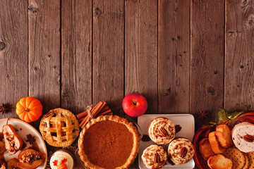 Autumn food bottom border. Table scene with a selection of pies, appetizers and desserts. Top view over a rustic wood background. Copy space.