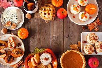 Autumn food frame. Table scene with a selection of pies, appetizers and desserts. Top view over a rustic wood background. Copy space.