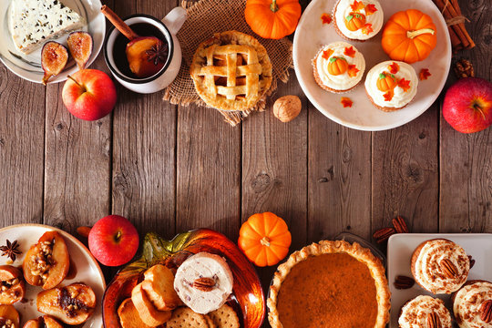 Autumn food double border. Table scene with a selection of pies, appetizers and desserts. Top view over a rustic wood background. Copy space.