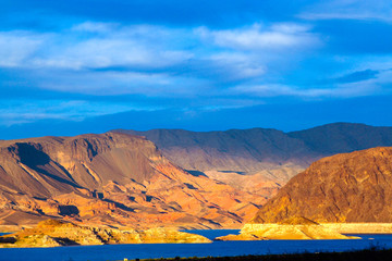 View over blue lake water on dry barren mountains in evening sunlight - Lake Powell, USA