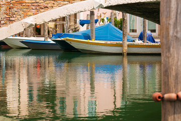 Boats under the old bridge in Chioggia town in venetian lagoon. Veneto, Italy, Europe.